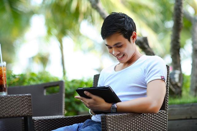 muž smějící se na obrazovku tabletu