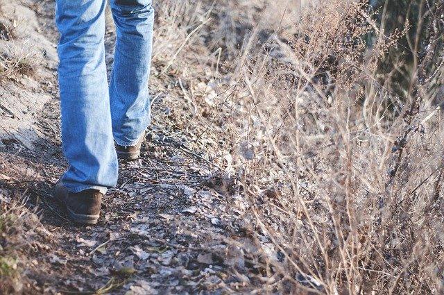 Mužské nohy jdoucí stezkou v přírodě